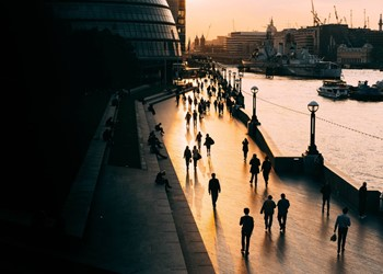 City river embankment at dusk with commuters